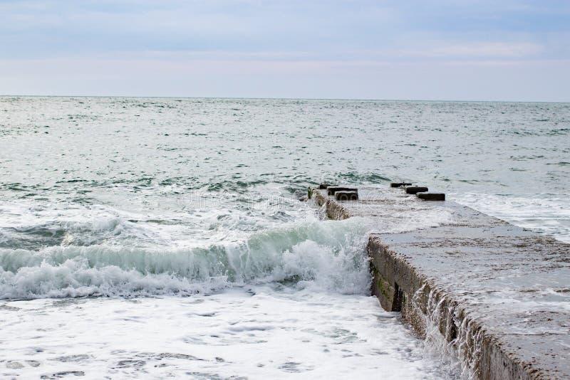 在海的波浪在码头阴云密布附近 免版税库存图片