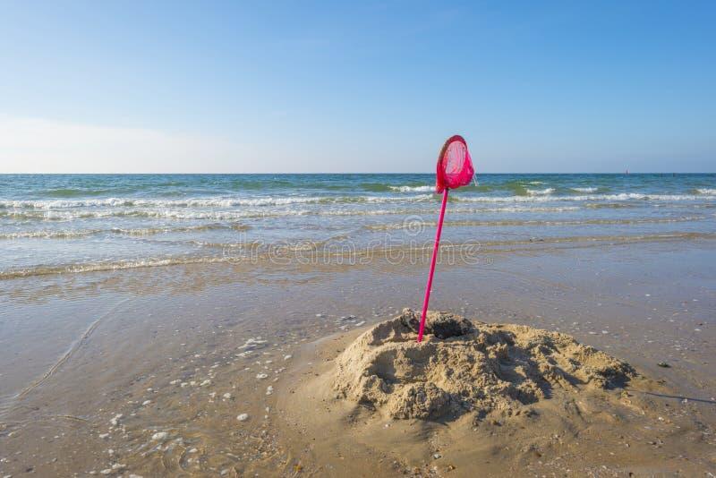 在海的浪潮威胁的海滩的沙子城堡 免版税库存图片