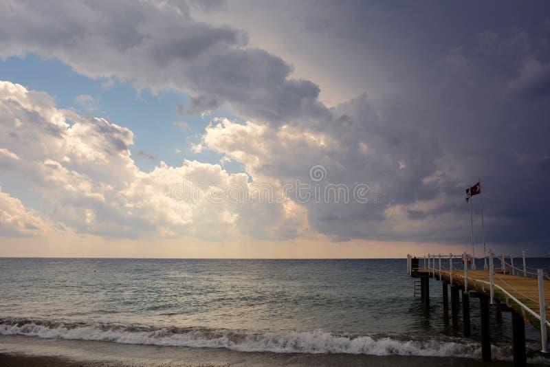 在海的码头日落和雨的在阿拉尼亚,土耳其 图库摄影