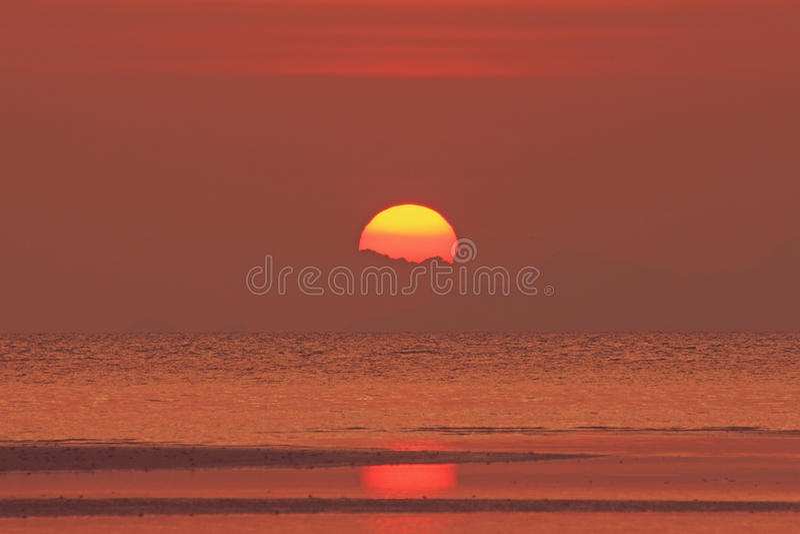 在海的红色日落有金黄轻的天空的 免版税库存图片