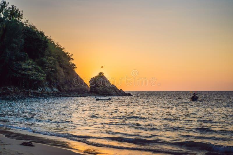在海的美好的日落在岩石后 免版税库存图片