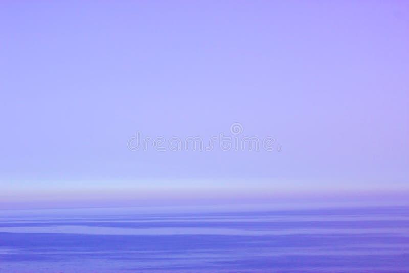 在海的美好的紫色日落 库存照片