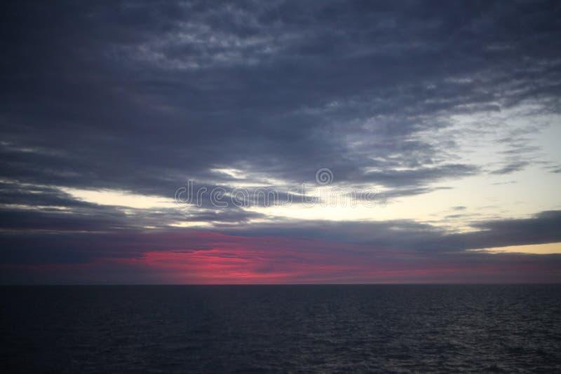 在海的美好的红色五颜六色的日出有剧烈的云彩和太阳发光的 免版税图库摄影
