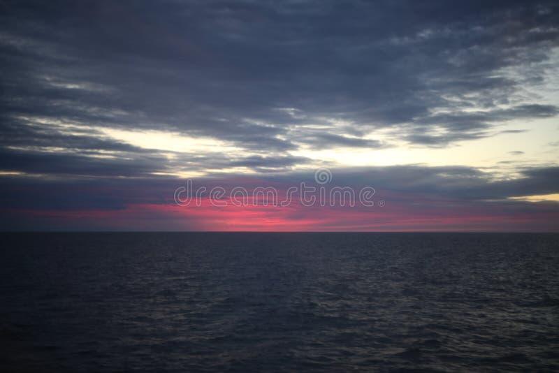 在海的美好的红色五颜六色的日出有剧烈的云彩和太阳发光的 库存照片