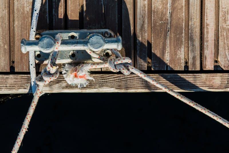 在海的背景的双重停泊的系船柱十字架游艇码头的 免版税库存照片