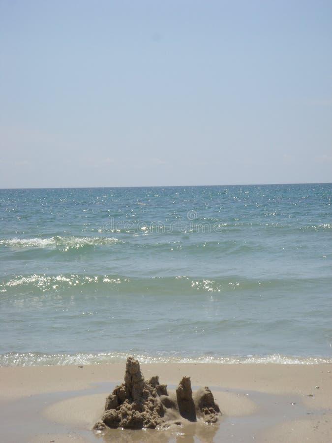 在海的背景的沙子城堡 免版税库存照片