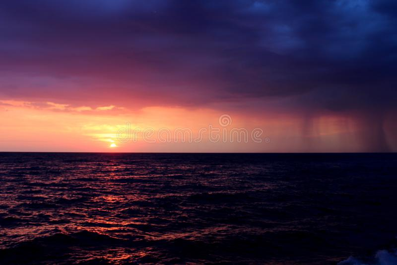 在海的雨日落的 免版税库存照片
