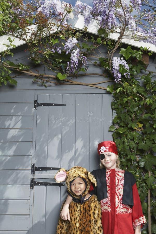 在海盗和捷豹汽车服装的孩子反对棚子 图库摄影