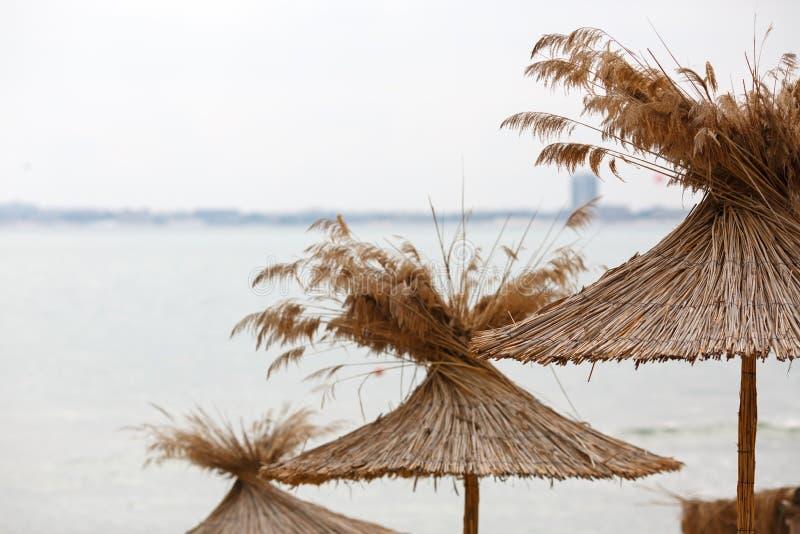 在海背景的秸杆伞 免版税库存照片