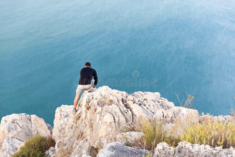 在海背面图上的人上升的岩石 免版税库存图片