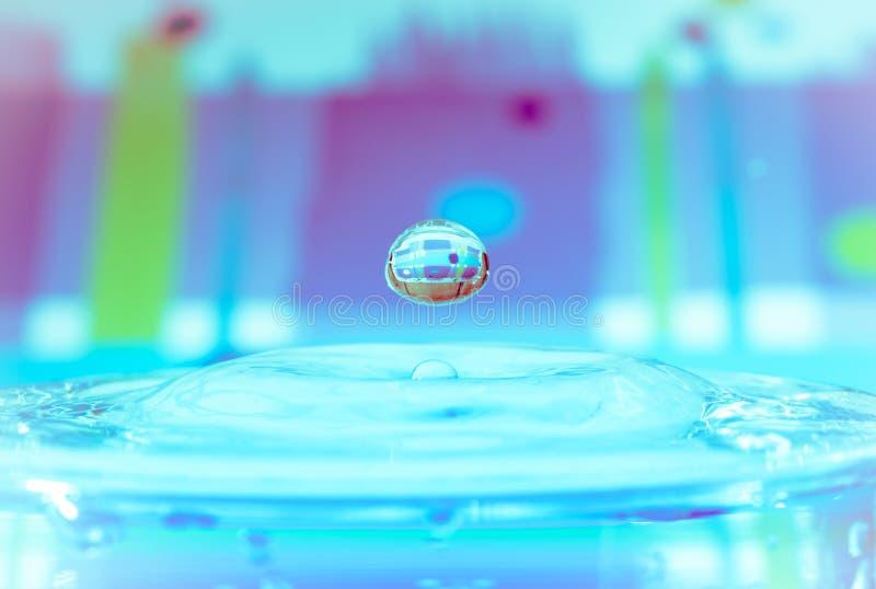 在海蓝色背景的下跌的水下落 免版税图库摄影