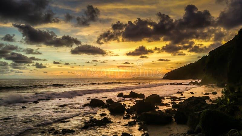 在海表面的风景日落 在热带Menganti海滩,加布棉,中爪哇省,印度尼西亚的美好的日落 免版税库存图片