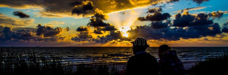 在海边剪影的愉快的爱恋的夫妇 库存图片