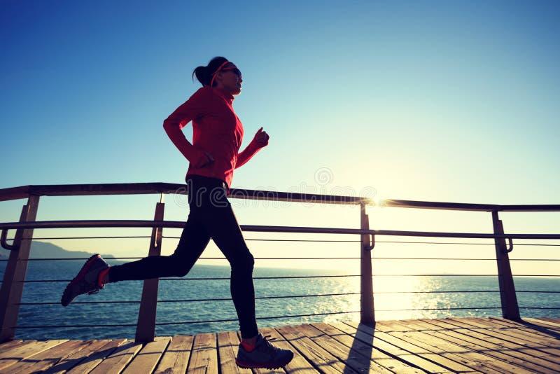在海边木板走道的运动的女性慢跑者早晨锻炼 库存照片