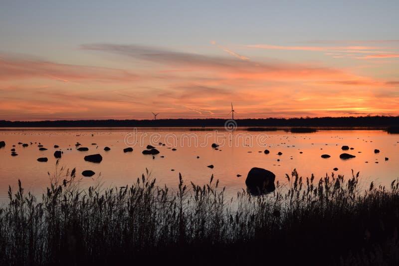在海边的浪漫日落与风车 免版税图库摄影