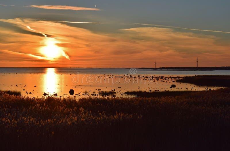 在海边的浪漫美丽如画的日落与风车 免版税库存图片