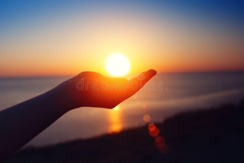 在海运日落 太阳在儿童` s手上 免版税库存照片