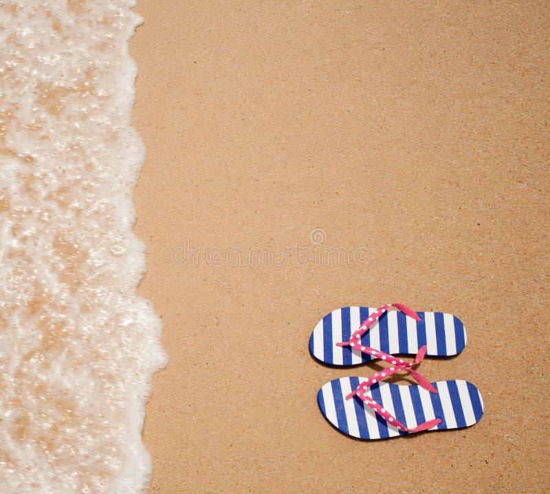 在海运海滩的五颜六色的塑胶人字平底拖鞋对 免版税库存照片