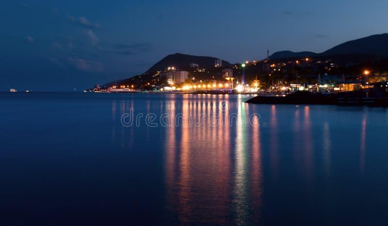 在海运附近的城市在晚上 免版税库存照片