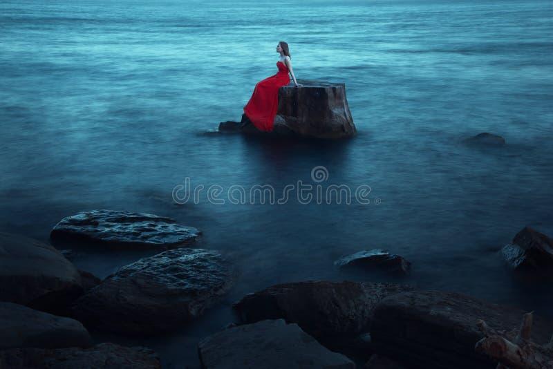 在海附近的一名哀伤的妇女在晚上 免版税库存图片