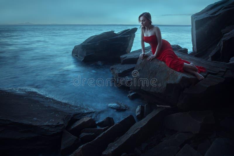 在海附近的一名哀伤的妇女在晚上 图库摄影