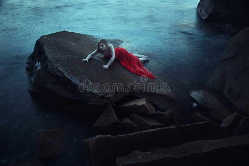 在海附近的一名哀伤的妇女在晚上 免版税图库摄影