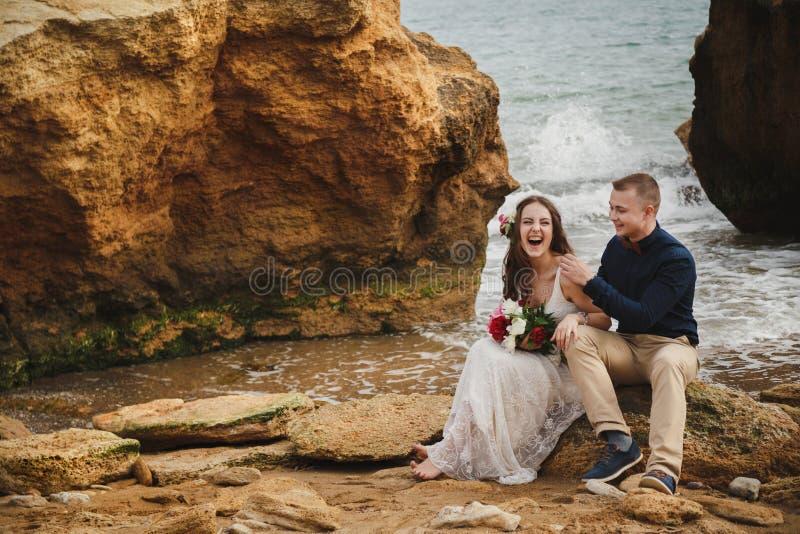 在海附近的室外海滩婚礼仪式,时髦的愉快的微笑的新郎和新娘坐石头,获得乐趣和 库存照片