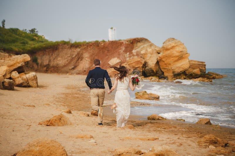 在海附近的室外海滩婚礼仪式,时髦的美丽的新郎和新娘去在海岸的婚姻的法坛 免版税库存图片