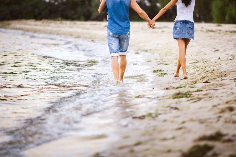 在海附近的家庭假日 在牛仔裤衣裳的两个成人有他们的胳膊的一个孩子的沿沙滩走从后面 免版税库存图片