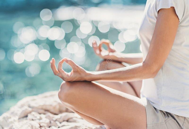 在海附近的年轻女人实践的瑜伽在夏天 和谐和凝思概念 免版税库存图片
