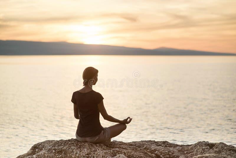 在海附近的年轻女人实践的瑜伽日落的 和谐、凝思和旅行概念 健康生活方式 图库摄影