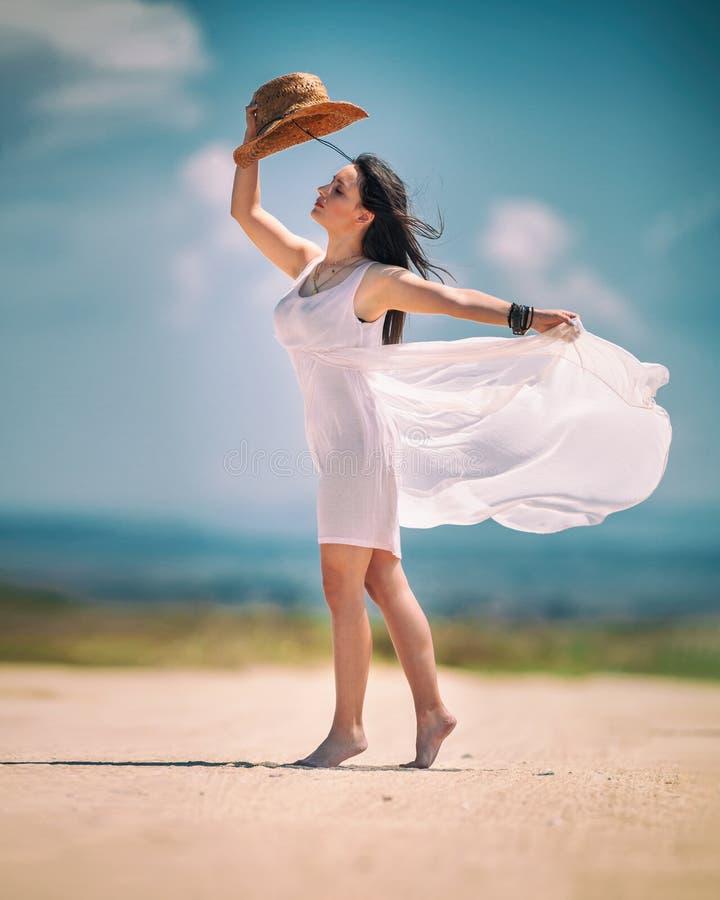 在海附近的美丽的少妇佩带的白色礼服 免版税图库摄影