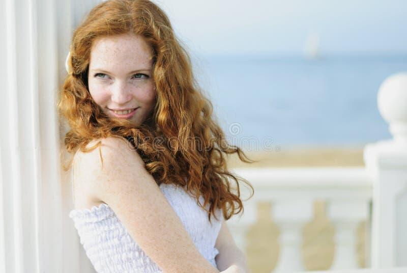 在海附近的美丽的红发女孩 免版税图库摄影