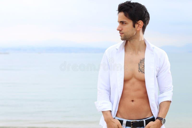在海附近的英俊的男性 免版税库存照片