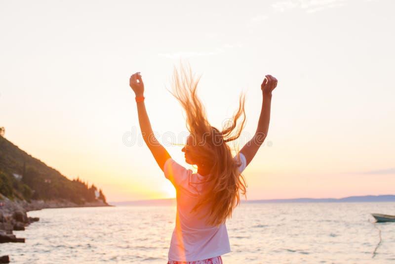 在海附近的beautyful妇女感觉自由见面的太阳 免版税图库摄影