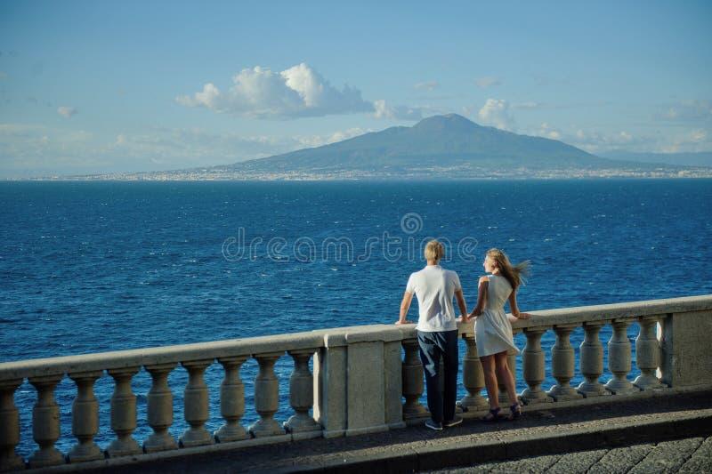 在海风景和维苏威,那不勒斯,意大利的背景的年轻浪漫夫妇 免版税图库摄影