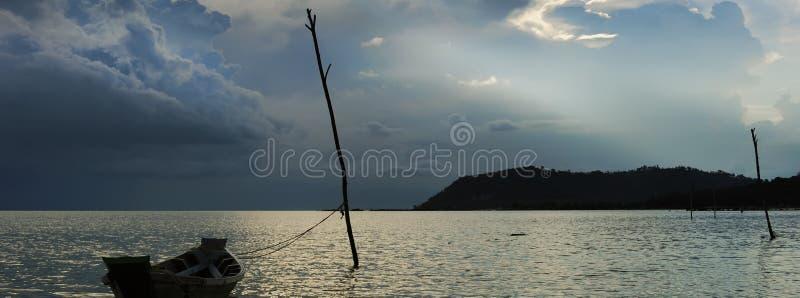 在海,偏僻的小船剪影的风雨如磐的云彩在水,在日落期间的剧烈的天空,没有人中 旅游业和旅行概念 免版税库存图片