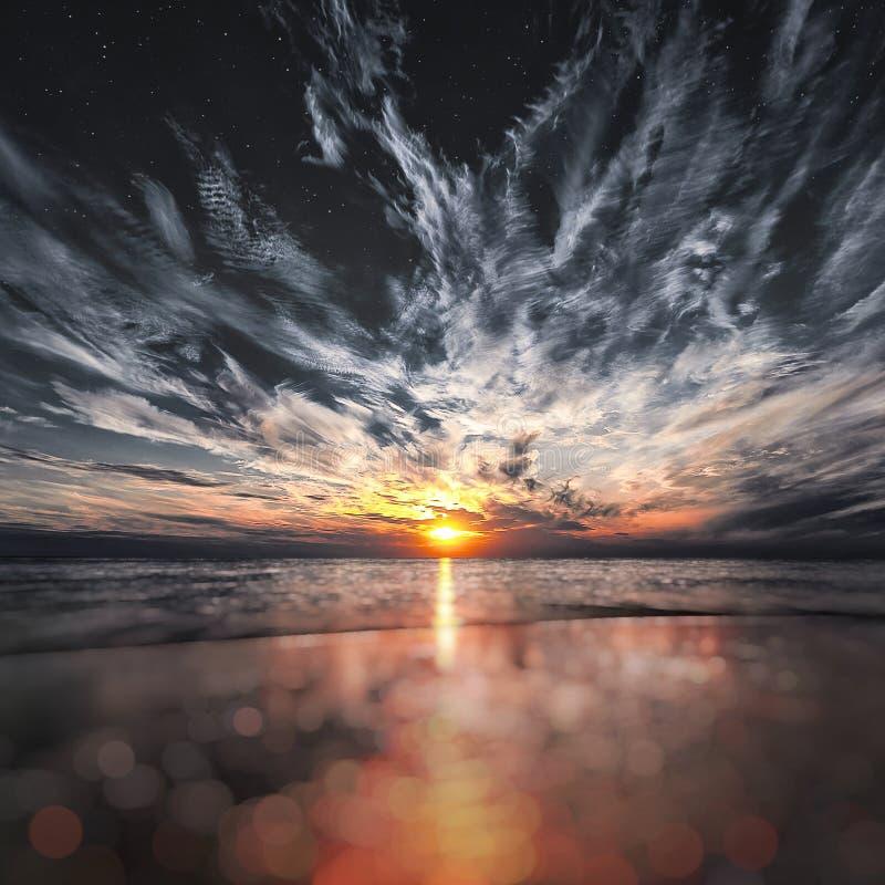 在海滩、星和月亮的美好的日落在天空 免版税库存图片