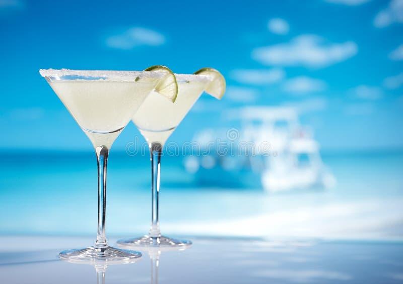 在海滩、蓝色海和天空背景的玛格丽塔鸡尾酒 免版税图库摄影