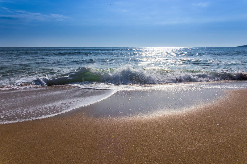 在海水以后日出和飞溅铺沙海海滩和蓝天 免版税图库摄影