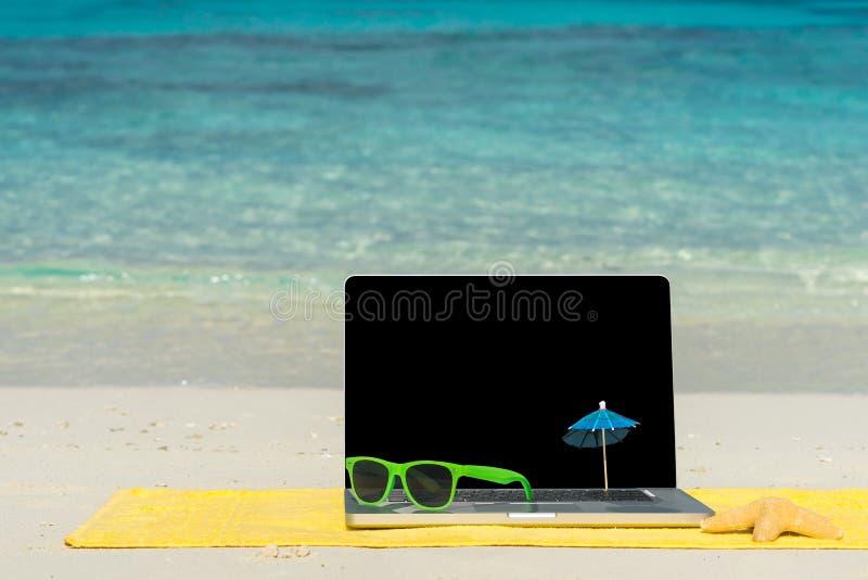 在海滩-商务旅游背景的计算机笔记本 免版税库存图片