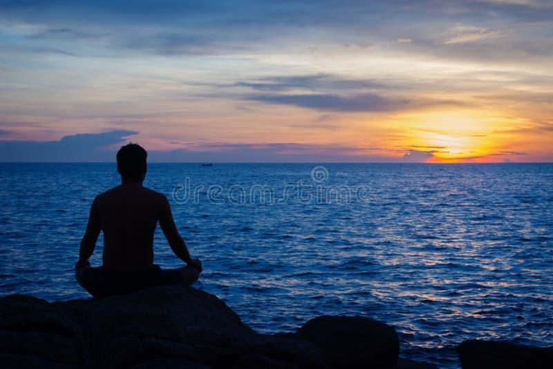 年轻在海洋岸的人实践的瑜伽 库存图片