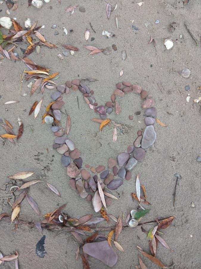 在海滩放置的石心脏 库存图片