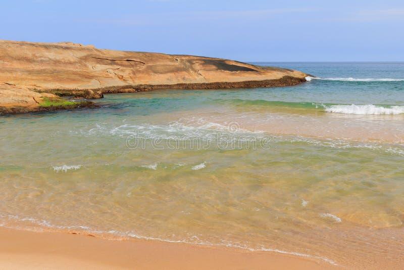 在海滩普腊亚的岩石做Cepilho用透明水,特林达迪, 免版税图库摄影