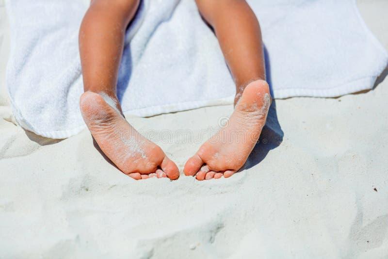 在海滩毛巾的儿童脚 免版税库存图片