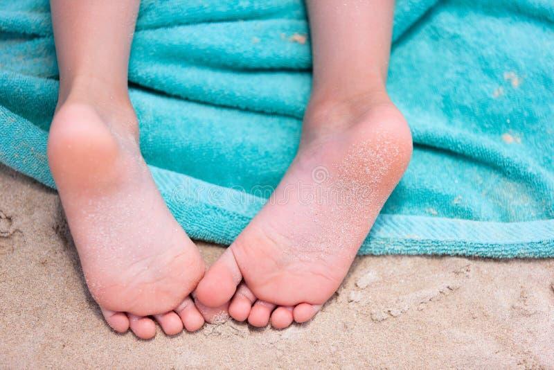在海滩毛巾的小女孩脚 免版税库存图片