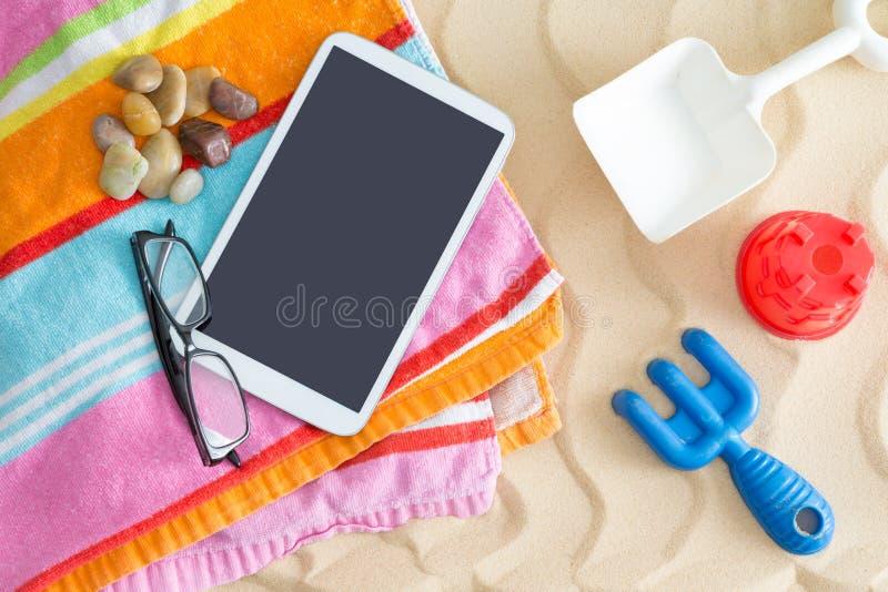 在海滩毛巾的片剂个人计算机与玻璃和玩具 免版税库存图片