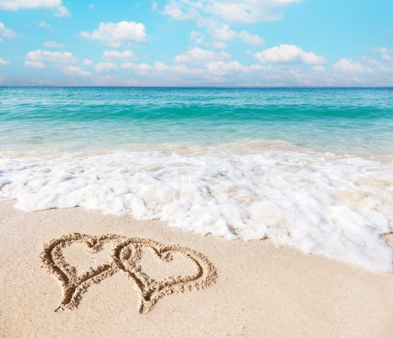 在海滩沙子画的心脏 库存图片