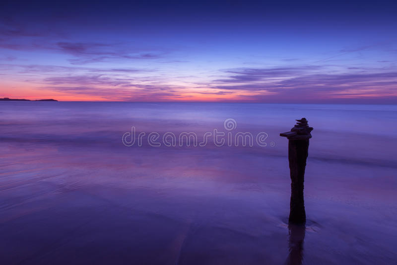 在海洋海滩海岸的镇静紫色日落 库存照片