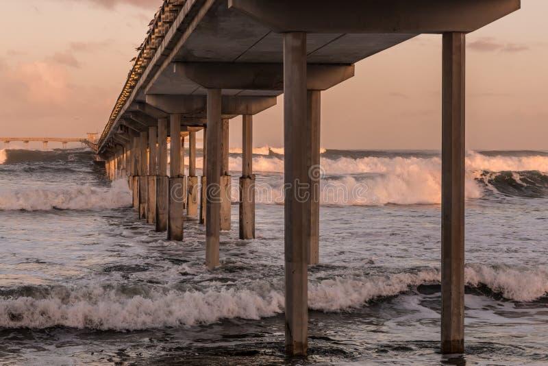 在海洋海滩渔码头下 免版税库存照片